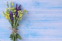 gula och lila vildblommor på en blå trätabell med ett ställe för inskrift Top beskådar royaltyfria bilder