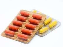 Gula och orange preventivpillerar för gelatinkapslar i blåsapacke Arkivbilder