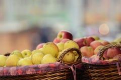 Gula och röda äpplen i träkorgar Arkivfoton