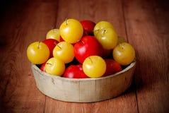 Gula och röda plommoner i bunke Arkivbilder