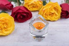 Gula och röda rosor och stearinljus på vit träbakgrund Royaltyfri Bild