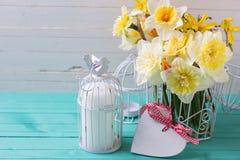 Gula påskliljablommor, stearinljus i dekorativ fågelbur och hea Arkivbilder