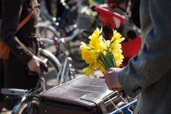 Gula påskliljor i handen av en man med en cykel Arkivfoto