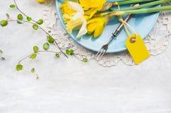 Gula påskliljor på blåttplattan med gaffeln och tabellen undertecknar, fjädrar garnering Royaltyfri Foto