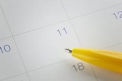 gula pennpunkter till numret 11 på kalenderbakgrund Arkivbild