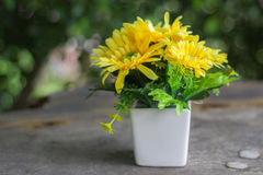 Gula plast- blommor med den vita krukan fotografering för bildbyråer
