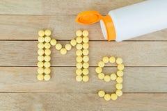 Gula preventivpillerar som bildar form till Mg-alfabetet på wood bakgrund Royaltyfri Fotografi