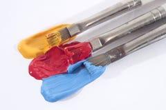 Gula röda och blåa akrylmålarfärger och målarpenslar Arkivbilder