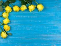 Gula rosor på blå träbakgrund Royaltyfria Foton