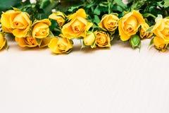 Gula rosor på en ljus träbakgrund Kvinnors dag, Valenti Arkivfoto