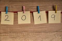 Gula sidor med numren av det nya året 2019 som hängs med kulöra klädnypor royaltyfria bilder