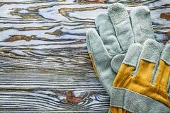Gula skyddande handskar på träbräde Fotografering för Bildbyråer