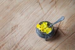 Gula små vildblommor i en tappninglerkärlbunke av en skednolla Royaltyfri Foto