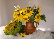 Gula solrosor i en keramisk vas på trätabellen med vit t Arkivfoto