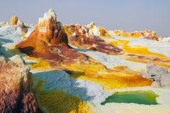 Gula svavel- volcanoes som sänder ut giftgas, fördunklar, svavel sätter in den Danakil för vita och gröna färger öknen, avlägsen  Royaltyfri Bild