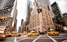 Gula taxis rider på den 5th avenyn i New York Arkivbild
