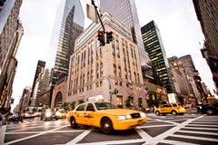 Gula taxis rider på den 5th avenyn i New York Arkivbilder