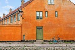 Gula väggar av historisk byggnad i traditionell stil i Köpenhamnen, Danmark Cykel parkerat gammalt hus för forntid arkivbild
