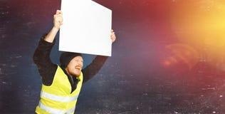 Gula västar för protester Den unga mannen rymmer en affisch med ljus på blå bakgrund royaltyfri bild