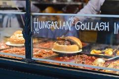 Gulaschsoppa med nötkött, potatis- och köttkorv, tjänade som i en brödbunke royaltyfri foto