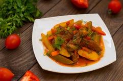 Gulasz z grulami, marchewkami, zalewami, pomidorami i gorącymi pieprzami, Azu Tartarian na białego kwadrata talerzu Drewniany wie Obraz Royalty Free