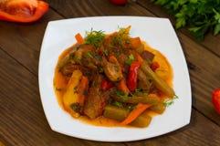 Gulasz z grulami, marchewkami, zalewami, pomidorami i gorącymi pieprzami, Azu Tartarian na białego kwadrata talerzu Drewniany wie Zdjęcia Stock
