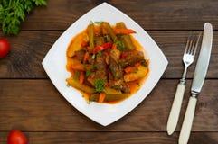 Gulasz z grulami, marchewkami, zalewami, pomidorami i gorącymi pieprzami, Azu Tartarian na białego kwadrata talerzu Drewniany wie Obrazy Stock