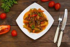 Gulasz z grulami, marchewkami, zalewami, pomidorami i gorącymi pieprzami, Azu Tartarian na białego kwadrata talerzu Drewniany wie Zdjęcie Royalty Free