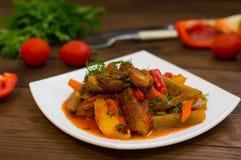 Gulasz z grulami, marchewkami, zalewami, pomidorami i gorącymi pieprzami, Azu Tartarian na białego kwadrata talerzu Drewniany wie Obraz Stock