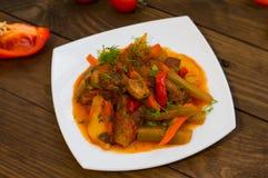 Gulasz z grulami, marchewkami, zalewami, pomidorami i gorącymi pieprzami, Azu Tartarian na białego kwadrata talerzu Drewniany wie Zdjęcie Stock