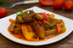 Gulasz z grulami, marchewkami, zalewami, pomidorami i gorącymi pieprzami, Azu Tartarian na białego kwadrata talerzu Drewniany wie Fotografia Royalty Free