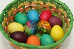Guld- ägg över grön lutningbakgrund Handgjorda målade ägg i korgen för påskberöm på vit bakgrund Påsk kulöra easter ägg kolonn Royaltyfri Fotografi