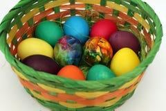 Guld- ägg över grön lutningbakgrund Handgjorda målade ägg i korgen för påskberöm som isoleras på vit bakgrund Påsk kulöra easter  Arkivfoto