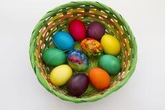 Guld- ägg över grön lutningbakgrund Handgjorda målade ägg i korgen för påskberöm som isoleras på vit bakgrund Påsk kulöra easter  Royaltyfri Foto