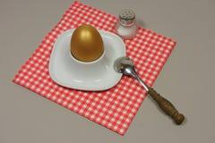 Guld- ägg i en äggkopp Arkivfoto