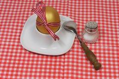Guld- ägg i en äggkopp Arkivbilder