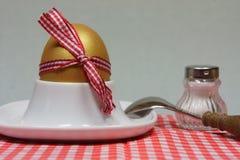 Guld- ägg i en äggkopp på en röd mönstrad servett Arkivfoton