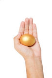 Guld- ägg i handen som isoleras på vit Royaltyfria Bilder