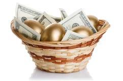 Guld- ägg och dollar i en isolerad korg Royaltyfria Foton
