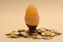 Guld- äggbegrepp med högen för guld- mynt Royaltyfri Bild