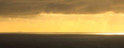 Guld- ändå molnig solnedgång på havet med ett endast skepp royaltyfri bild