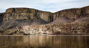 Guld- ökenkant som eroderar med tid över en flod royaltyfria bilder