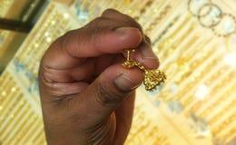 Guld- örhänge i hand royaltyfri foto