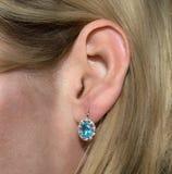 Guld- örhänge med den blåa ädelstenen - topas och få diamanter i modell` s fotografering för bildbyråer