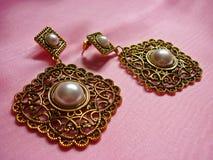 Guld- örhängen med pärlor, tappningstil Arkivfoton