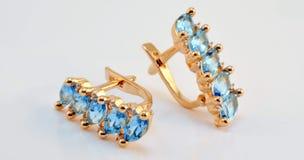 Guld- örhängen med schweiziska topasmellanlägg Royaltyfria Foton