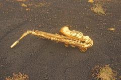 Guld- Alto Saxophone Lies på den svarta bakgrunden Romantiker och royaltyfri fotografi