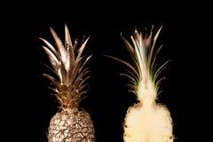 Guld- ananasskivor på svart bakgrund Royaltyfria Foton
