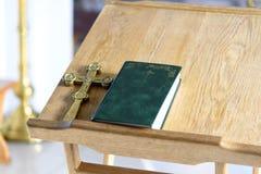 Guld- argt kors med bibeln på trätabellen Kristen chur arkivbild