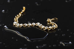 Guld- armband med stenar på en svart plast- bakgrund Royaltyfria Bilder